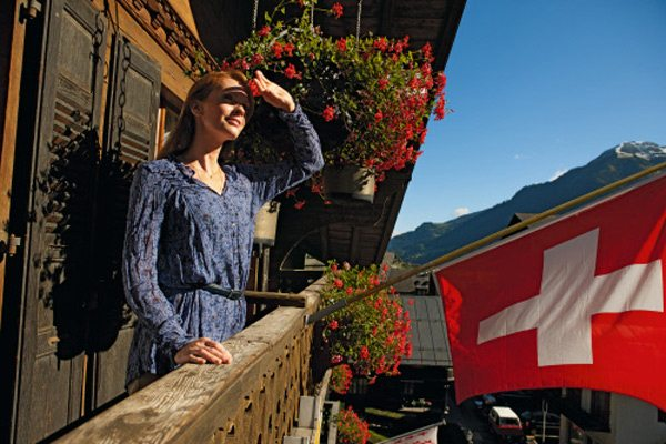 Frau steht auf dem Balkon eines Hotels in der Schweiz