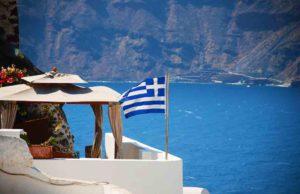 Nationalhymne: Yacht mit griechischer Fahne vor Insel Santorin