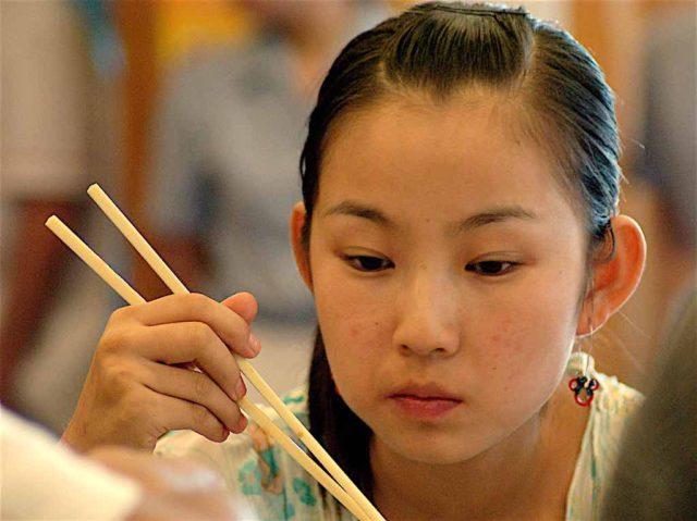 So ticken Chinesen: Mädchen beim Essen mit Stäbchen