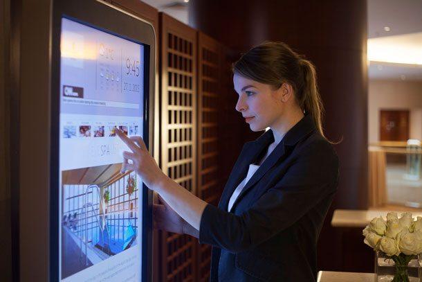 Meeting-App: Frau tippt auf großes Display im Corinthia Hotel Prag