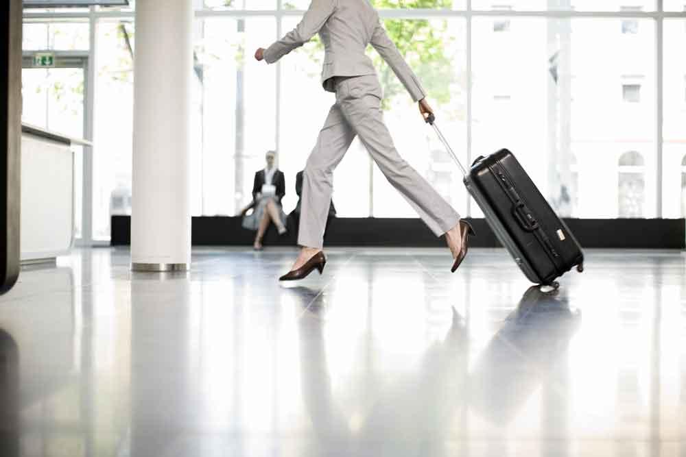 Frau eilt mit ihrem Gepäck zum Check-in