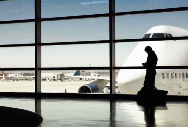 Trends bei Geschäftsreisen: Mann wartet am Gate auf seinen Flug