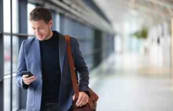 Geschäftsreise: Mann mit Smartphone am Flughafen