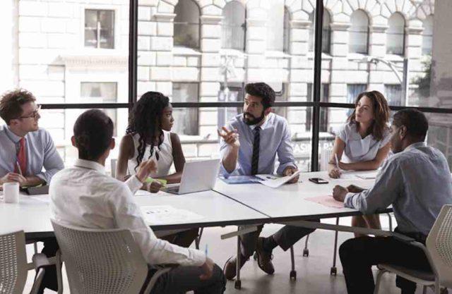 Travel Management: Menschengruppe sitrzt am Tisch