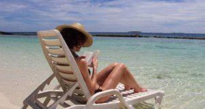 Fernreise: Frau auf Sonnenliege am Strand auf den Malediven