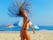 Reisen: Frau am Strand, wirft Kopf mit Boxbraids zurück