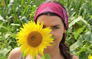 Gesundheits- und Medizinreisen: Frau mit Sonnenblume vor Gesicht