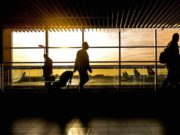 Flugreisende in der Wartehalle am Flughafen