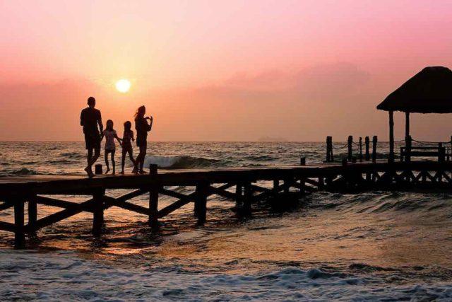Urlauber: Familie auf einem Bootssteg bei Sonnenuntergang