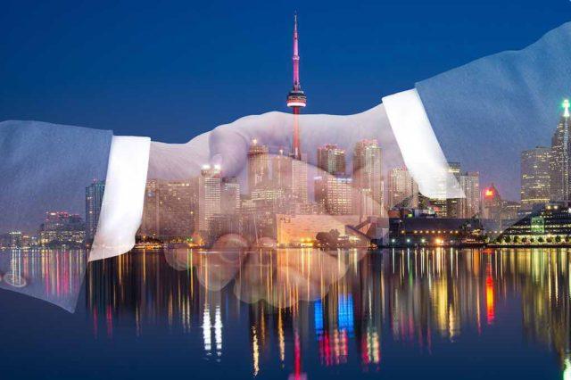 Concur hat neuen Namen: Händeschütteln vor einer Skyline