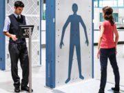 Frau steht im Körperscanner, Mann kontrolliert Bildergebnis