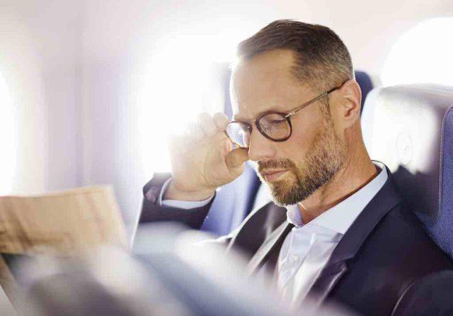 Langstreckenflügen Mann liest in der A350 Economy Class