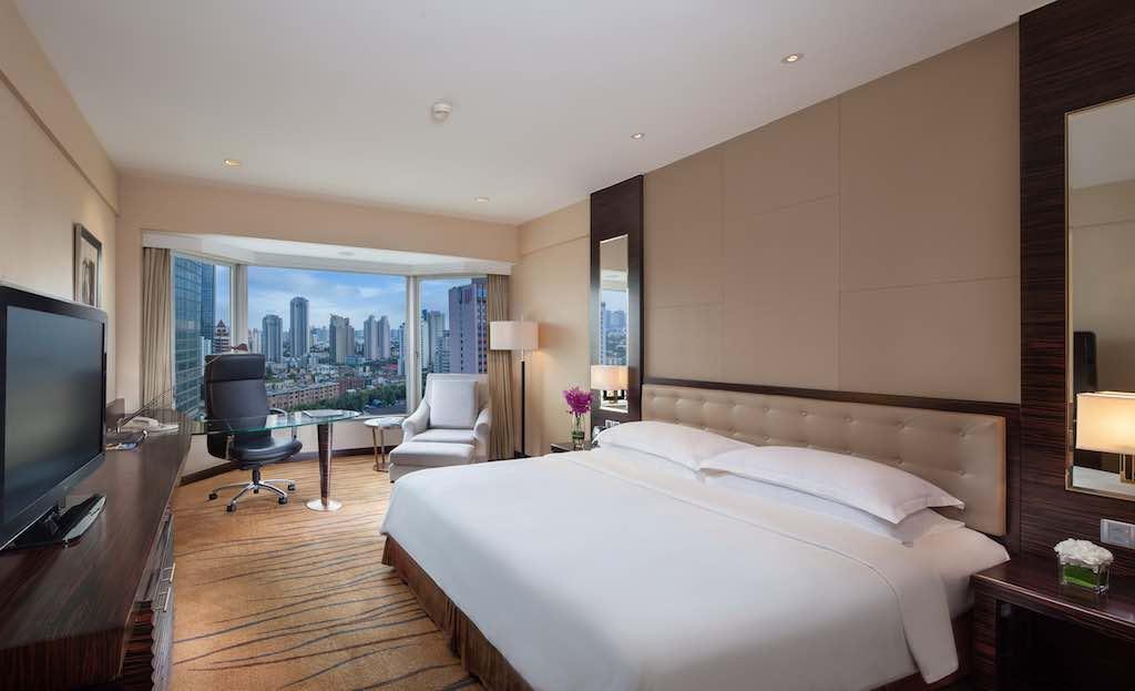 Zimmer im Hotel The Kunlun Jin Jang in Shnaghai mit Blick aufs Bett und die Stadt