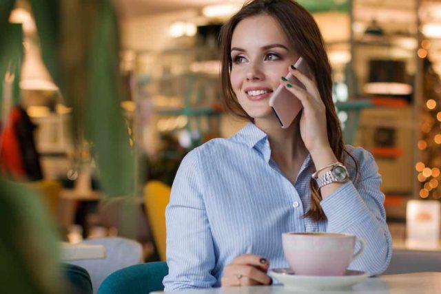 Mritim Hotels: Frau telefoniert mit Smartphone in einem Lokal