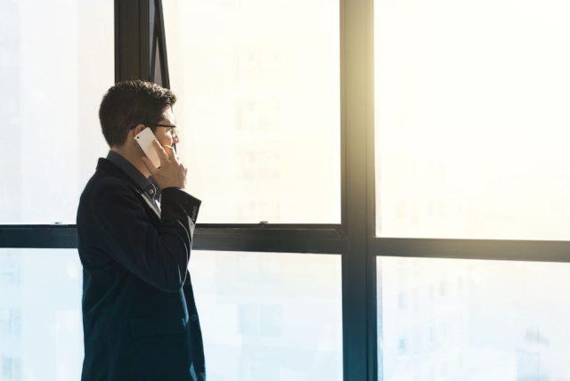 Mann steht am Fenster und ruft eine Firma an