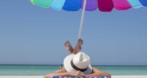 Frau liegt auf Sonnenliege unter einem bunten Sonnenschirm