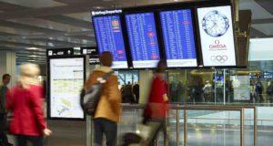 Flüge umbuchen: Menschen vor Hinweistafeln am Flughafen Zürich