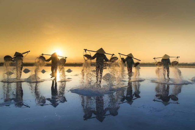 Nachhaltigkeit im Tourismus: Menschen bei Salzgewinnung in Vietname