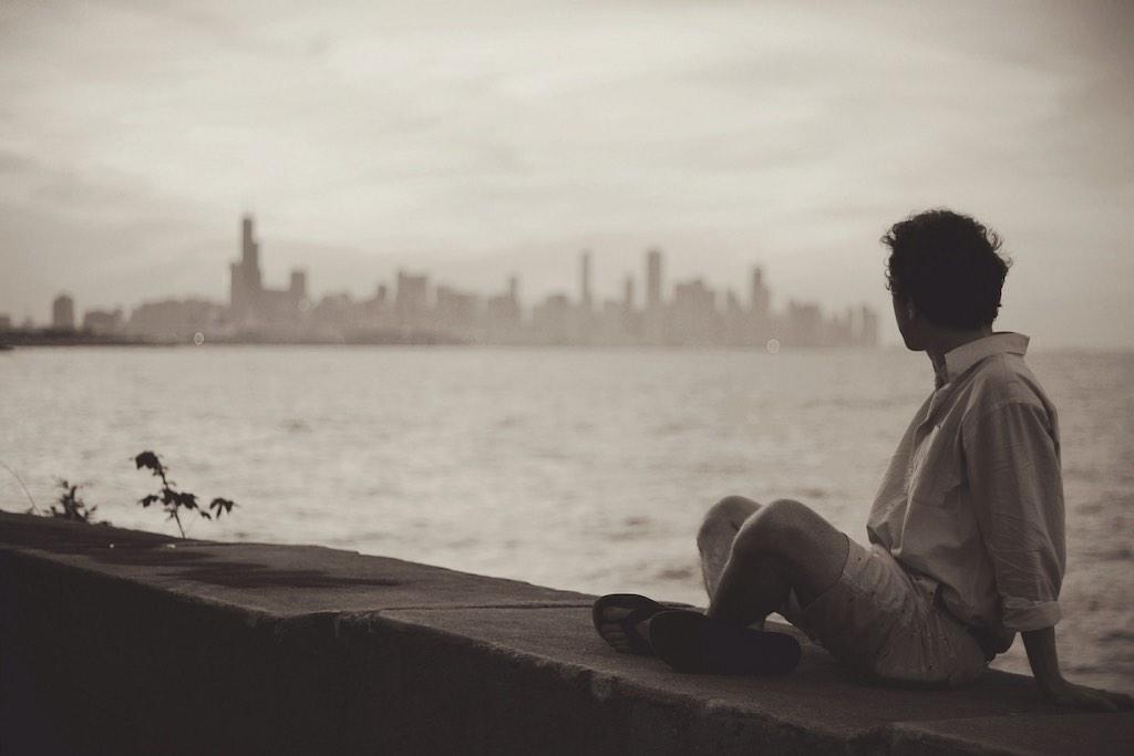 Mann sitzt auf Kaimauer und schaut zur City am Horizont