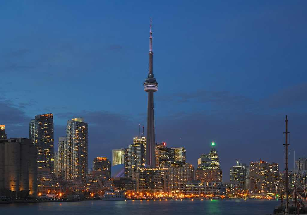 Skyline von Toronto und Harbourfront bei Abenddämmerung: CN Tower und die Skyline der Donwtown. Man erkennt u.a. folgende Bauwerke: Walter Carsen Centre, Rogers Centre, First Canadian Place, Scotia Plaza, Brookfield Place (Foto: Wladyslaw CC BY-SA 3.0], via Wikimedia Commons)
