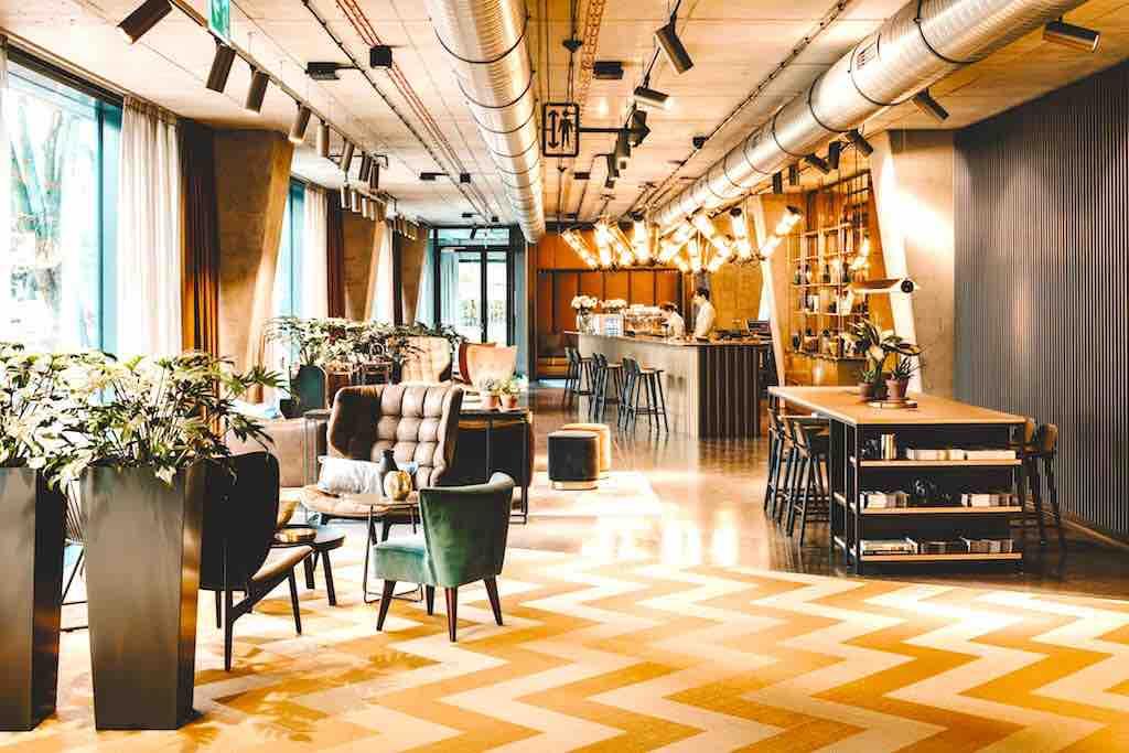 Neues Hotel Vienna House Mokotow: In der Lobby gibt es zwei Tische zum Arbeiten und für den Self-Check-in/-out sowie verschiedene Sitzbereiche (Foto: © Vienna House)